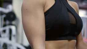 Attractive sportswoman training with dumbbells at the gym. Close up of pretty female athlete raising her arms to the. Sides. Strong girl smiling for the camera stock video