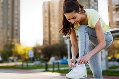Attractive sportswoman tying shoelace and getting ready for fitness Royalty Free Stock Images