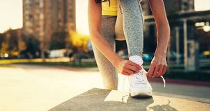Attractive sportswoman tying shoelace and getting ready for fitness. Attractive young sportswoman tying shoelace and getting ready for fitness Royalty Free Stock Photos
