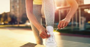 Attractive sportswoman tying shoelace and getting ready for fitness. Attractive young sportswoman tying shoelace and getting ready for fitness Stock Photography
