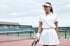 Are you ready to lose? Beautiful girl is going to play tennis on the court royalty free stock photography