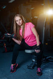 Attractive sporty girl doing workout with dumbbells in gym. Beautiful fitness woman working on her biceps. Attractive sporty girl doing workout with dumbbells stock image