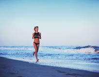 Attractive sporty girl run along the beach at amazing sunset with sea on background. Athletic girl running along the beach on amazing orange sunset background royalty free stock images