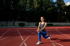 Attractive sporty girl stretching before running at the stadium. Empty space stock images