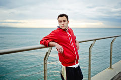 Attractive sporty runner in red sport hoodie stands on the pier leaning on the rail and look away. Morning jogging, fitnes and healthily lifestyle, sport and stock photos