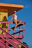 Swimsuit model sitting at the lifeguard tower. Royalty Free Stock Photography