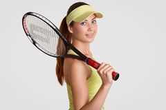 Attractive sporty woman with clean skin, wears casual clothing, holds tennis raquet, has pony tail, being active player, isolated. Over white background. People stock images