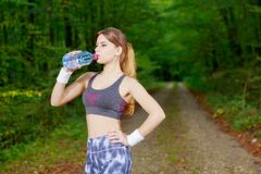 Attractive sporty woman drinking water from a bottle Royalty Free Stock Photos