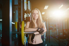 Attractive sporty woman exercising with barbell in gym. Beautiful fitness girl resting after sport workout exercises. Blonde femal Stock Photography