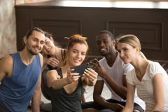 Attractive sporty woman holding phone taking group selfie at tra Stock Photography