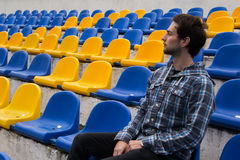 Attractive sporty young man model in blue shirt sitting on blue stadium seats after training staring at field. Perspective view on stadium chairs. Toned whites Royalty Free Stock Image