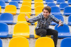 Attractive sporty young man model in blue shirt sitting on blue stadium seats after training staring at field. Perspective view on stadium chairs. Toned whites Stock Photos