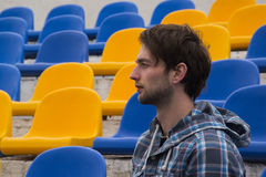 Attractive sporty young man model in blue shirt sitting on blue stadium seats after training staring at field Stock Photos
