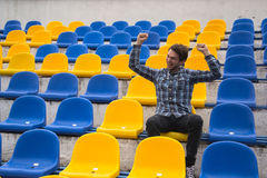Attractive sporty young man model in blue shirt sitting on blue stadium seats after training staring at field Stock Images