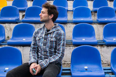 Attractive sporty young man model in blue shirt sitting on blue stadium seats after training staring at field Royalty Free Stock Images