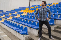 Attractive sporty young man model in blue shirt sitting on blue stadium seats after training staring at field. Perspective view on stadium chairs. Toned whites Stock Images