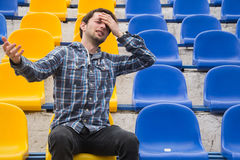 Attractive sporty young man model in blue shirt sitting on blue stadium seats after training staring at field. Perspective view on stadium chairs. Toned whites Stock Image