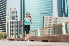 Attractive sporty young woman running on pavement.  Royalty Free Stock Photos