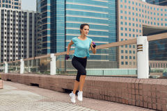 Attractive sporty young woman running on pavement Royalty Free Stock Photography