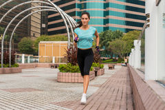 Attractive sporty young woman running on pavement.  Royalty Free Stock Photography