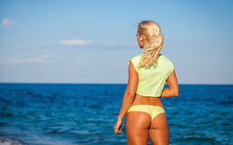 Attractive sporty young woman standing on the beach Royalty Free Stock Images