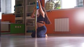 Attractive sporty young woman stretching and warming up on pole in a fitness class stock video footage