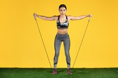 Attractive sporty young woman workout with stretch bands on the green grass over yellow background. Attractive sporty young woman workout with stretch bands on royalty free stock photo