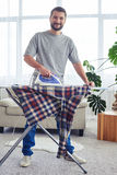 Attractive spouse ironing diligently shirt on board Royalty Free Stock Image
