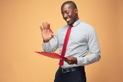 Attractive standing Afro-American businessman writing notes Stock Images