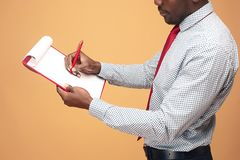 Attractive standing Afro-American businessman writing notes Royalty Free Stock Photos