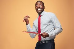 Attractive standing Afro-American businessman writing notes Stock Photos