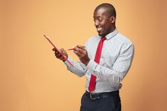 Attractive standing Afro-American businessman writing notes Royalty Free Stock Photo