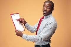 Attractive standing Afro-American businessman writing notes Stock Photo