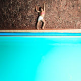 Attractive standing woman on pool edge. Royalty Free Stock Image