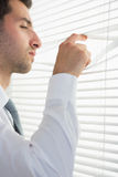 Attractive stern businessman spying through roller blind Stock Photo