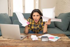 Attractive stressed woman managing finances, reviewing bank accounts, paying bills using laptop stock image