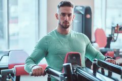 Young pensive bodybuilder in green shirt is doing exercises on training apparatus royalty free stock photo