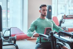 Young pensive bodybuilder in green shirt is doing exercises on training apparatus royalty free stock image