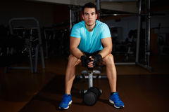 Attractive strong man taking break after fitness training in gym Royalty Free Stock Photography