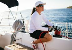 Attractive strong woman sailing with her boat Stock Photography