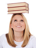 Attractive student balancing pile of books Royalty Free Stock Photos