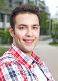 Attractive student with checked shirt laughing at camera Stock Photo