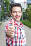 Attractive student with checked shirt showing thumb up. Attractive student with checked shirt standing on campus and showing thumb up with university building Stock Photos