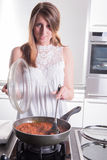 Attractive student cooking bolognese sauce in kitchen Royalty Free Stock Photo