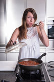 Attractive student cooking bolognese sauce in kitchen Royalty Free Stock Image