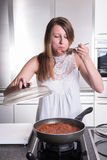 Attractive student cooking bolognese sauce in kitchen Royalty Free Stock Images