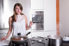 Attractive student cooking bolognese sauce in kitchen Stock Images