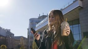 Attractive student girl drinking a milk cocktail while walking in the city`s park and listening to music through the app stock footage