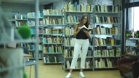 Attractive student girl reading book in library. Attractive student girl brunette reading book in library stock footage