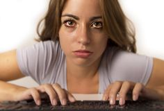 Attractive student girl or working woman sitting at computer desk in stress with tired red eyes after long hours working looking a. Young attractive student girl Royalty Free Stock Photos